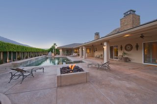 In ground pool in ranch style home courtyard bordered by long tree hedge.