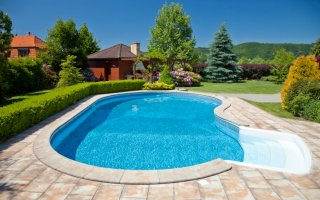 Kidney-shaped swimming pool with sanded brick patio and hedge
