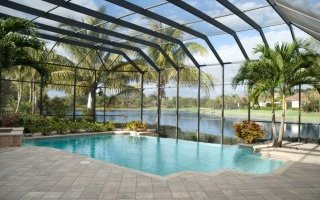 Screen-covered in-ground pool in Florida backyard surrounded by grey brick patio
