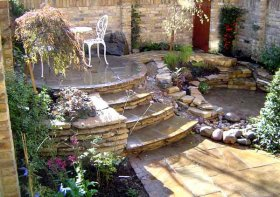 stone patio design with stone steps to pond